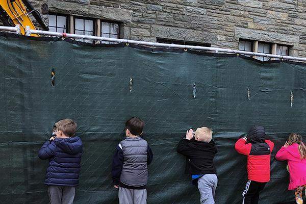 Children peering through to the construction zone.